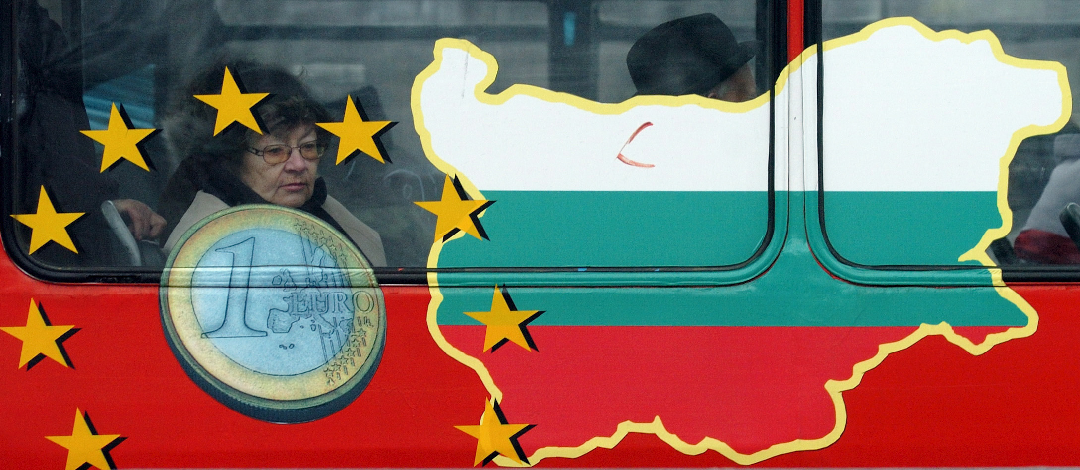 epa00895299 A Bulgarian woman stares out of a window of a city tram that carries an advertisement depicting the Euro currency and a map of the country, in Sofia Wednesday 3rd January 2007.  Bulgaria joined the E.U. on Monday, taking the bloc to 27 member countries.Bulgaria is set to switch to euro currency in 2010 at the earliest, the governor of the Bulgarian National Bank (BNB) Ivan Iskrov said  EPA/VASSIL DONEV
